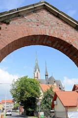 Eingang, Torbogen vom Friedhof in   Peterswaldau / Pieszyce, im Hintergrund die Türme der St.-Antonius-Kirche.