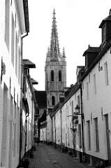 Blick durch die historische Straße Klein  Begijnhof in der belgischen Stadt Leuven/Löwen zur Sankt Gertrude Kirche / Sint Geertrui. Die Kirche   wurde im 14. bis 16. Jahrhundert als Pfarrkirche errichtet, der  71 m hoher Turm mit durchbrochener Stein