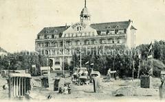 Historische Fotografie vom Kurhaus in Brunshaupten an der Ostsee; am Strand stehen Strandkörbe in Sandburgen, eine Frau liegt bekleidet auf einer Liege in der Sonne.