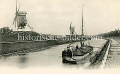Historische Fotografie vom Kanal Gent-Osstende; ein Schiff liegt am Kanalufer in Brügge, daneben verläuft der gepflasterte Treidelpfad. Auf der ehemaligen Befestigungsanlage von Brugge stehen zwei Windmühlen