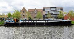 Ein Binnenschiff liegt am Kolenkaai des Gent- Oostende Kanals  in Brügge; am Kanalufer stehen moderne und historische Gebäude.