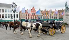 im historischen Zentrum der Stadt Brügge - alte flämische Architektur als Randbebauung, Pferdedroschken warten auf Touristen.