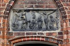 Sandsteinrelief mit Geißelung und Kreuzigung Christi über dem Eingang der Beguinenhaus - Hospitalkapelle aus dem Mittelalter am Salzmarkt in der Hansestadt Havelberg.