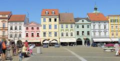 Historische Randbebauung am Marktplatz in der Innenstadt von Budweis  / České Budějovice; Wohn und Geschäftshäuser mit farbiger Fassade und Colonnaden.