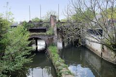 Ruine eines alten Sperrwerks mit bewachsenen Ziegelmauern an dem Fluss Dijle in der Innenstadt von Löwen/Leuven.