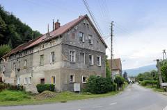 Dorfstraße entlang des Baches Kamionka in Pieszyce / Peterswaldau; einzelne Wohnhäuser - im Hintergrund bewaldete Berge vom Eulengebirge.