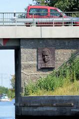 Straßenbrücke über den Havelkanal bei Brieselang, erbaut 1952 - Gedächnisplakette, Bronzeplatte mit Reliefportrait von Nikos Belogiannis /  Belojannis - griechischer Kommunist und Widerstandskämpfer - hingerichtet 1952 in Griechenland.
