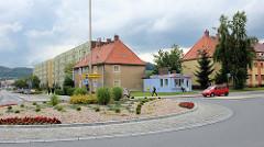 Wohnhäuser und kleiner rechteckiger Geschäftsbau an einem Kreisverkehr in der polnischen Stadt Langenbielau/Bielawa.