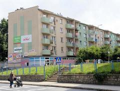 Wohnblock mit farblich abgesetzten Balkons und Werbung an der Hausfassade in der Straße Tadeusza Kościuszki  von    Pieszyce / Peterswaldau.