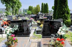 Friedhof in   Peterswaldau / Pieszyce - Grabsteine mit eingravierten Heiligendarstellungen und Grabschmuck mit Plastikblumen.