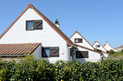 Einzelhäuser in gleichem Baustil mit angebautem Schuppen und Holzluken beim Gent-Oostende-Kanal bei Brügge.