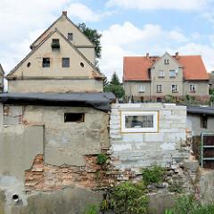 Alter Schuppen und Neubau am Ufer des Baches Kamionka in Pieszyce / Peterswaldau.