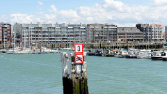 Sportboote - Segelboote und Motorboote - liegen in der Marina von Seebrügge; an der Hafenpromenade mehrstöckige Gebäude kleinen Ferienwohnungen. Vordergrund eine Holzdalbe mit einem Hinweisschild, das ein fahrende  Boote keinen Wellenschlag verursac