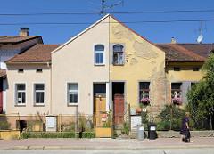 Alt und neu, Kontraste in der Architektur -Wohnhaus mit unterschiedlich gestalteter Fassade in   Budweis /  České Budějovice. Die eine Seite des Doppelhauses ist frisch restauriert, auf der anderen Seite bröckelt der Putz ab und die Ziegelsteine de