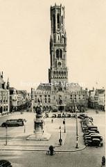 Altes Bild vom Großen Markt im Zentrum von Brügge - Blick auf den Brügger Belfried; erbaut im 13. Jahrhundert. Autos parken auf dem Grote Markt. Im Vordergrund das Denkmal für Jan Breydel und Pieter de Coninck.