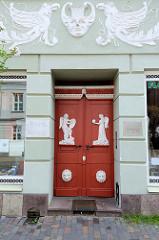 Klassizistische Eingangstür eines Geschäfts und Wohnhauses am Markt in Güstrow, allegorische Figuren stehen auf einem Sockel auf dem Türblatt der Doppeltür. Die Fassade des denkmalgeschützten Gebäudes ist mit Stuckgreifen / Vögeln versehen.
