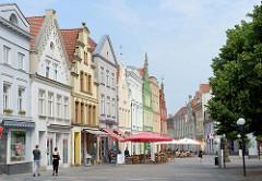 Historische Häuserzeile / Wohn und Geschäftshäuser am Markt in Güstrow; farbige Hausfassaden und Cafés auf dem Marktplatz.