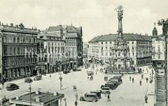 Altes Foto vom Marktplatz und der Dreifaltigkeitssäule in  Olmütz / Olomouc.  Auf dem Platz stehen PKW, am Straßenrand Pferdefuhrwerke.