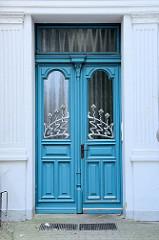 Alte Eingangstür im Stil des Historismus - aufgesetzte Zierverleistung und Jugensstil-Fenstergittern;  Bilder der restaurierten Altstadt von Güstrow.