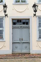 Eingang eines denkmalgeschützten Wohnhauses in der Kerstingstraße von Güstrow; Doppel-Holztür mit Dekorverleistung und klassizistischen Schmucktürgriff / Schlüsselschild
