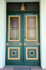 Alte Eingangstür im Stil des Historismus - farblich abgesetzte Zierverleistung und Schnitzerei, farbiges Fensterglas; Bilder der restaurierten Altstadt von Güstrow.
