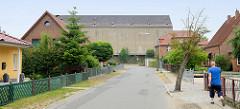 Einzelhäuser /Wohnhäuser im Werkweg von Güstrow, Blick auf die graue fensterlose massive Fassade eines Lagergebäudes Sankt Jürgens Weg.