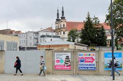 Mauer mit bunten Werbeplakaten, großes Eisentor eines Gewerbehofes - im Hintergrund die barocken Türme der Jesuiten Kirche Maria Schnee/Kostel Panny Marie Sněžné .