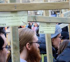Trauermarsch der Graswurzelbewegung Extinction Rebellion XR am Rathausmarkt in Hamburg. Holzkreuze mit der Aufschrift ausgestorbener Tier- /  Planzenarten - Schlangenadler / Verkanntes Filzkraut.