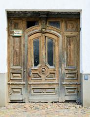 Alte Holztür ohne Farbe im Stil des Historismus - aufgesetzte Zierverleistung;   Bilder ausder Altstadt von Güstrow.