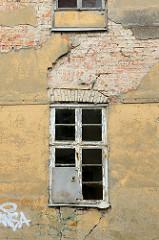 Hausruine mit zerbrochenen Fenster und abbröckelnder Putz, teilweise sind Mauersteine zu sehen; Fotos der Architektur in der Stadt Güstrow.