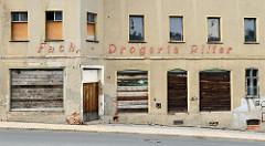 Leerstehendes Rauputzgebäude  in der Straße Schmöllnschen Vorstadt von Altenburg; Geschäft mit vernagelten Fenster und Eingang einer ehemaligen Fachdrogerie Ritter.