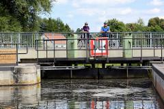 Geschlossenes Schleusentor der Schleuse Schöpfurth am Finowkanal; die Schleusenkammer hat eine Länge von 41m und einen Hub von 3,60m. Auf der Fussgängerbrücke stehen FahrradfahrerInnen und sehen der Schleusung zu.