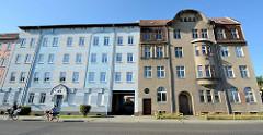 Mehrstöckige Wohnhäuser in Eberswalde, teilweise restauriert mit farbig abgesetzter Fassade sowie Wohnhaus mit Rauhputzfassade.
