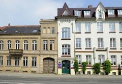 Restauriertes Wohn- und Gewerbegebäude mit weißer Fassade in der Eisenbahnstraße von Güstrow, links daneben ein leer stehendes Gebäude mit grauer Fassade und alter Holztür sowie Balkon mit Zierbrüstung.