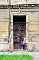 Alte Holztür / Doppeltür mit aufwändigem Schnitzwerk, eingerahmt von Stuck Dekoration- renovierungsbedürftiger Hausfassade, Wohnhaus  Olmütz /Olomouc.
