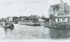 Historische Hafenszene am Finowkanal in Eberswalde, Arbeitsboote liegen am Kai - ein Frachtkahn wird auf dem Wasser gezogen.
