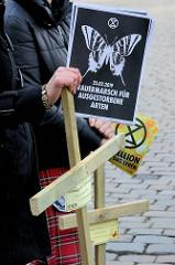Trauermarsch der Graswurzelbewegung Extinction Rebellion XR am Gerhart-Hauptmann-Platz in Hamburg. Flugblätter  mit Schmetterling - Trauermarsch für ausgestorbene Arten - Holzkreuze, Rebellion für das Leben.
