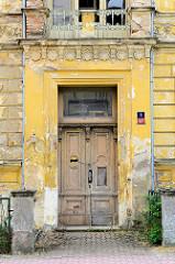 Holztür mit einer Kette verschlossen, renovierungsbedürftige Fassade eines verlassenen Gebäudes in   Marienbad / Mariánské Lázně.