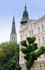 Kupferhelm / Kuppel vom Eckturm eines Gründerzeitgebäudes, dahinter der Kirchturm vom Wenzelsdom in Olmütz / Olomouc.