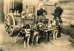 Milchhändlerin mit Haube - Polizist bei der Kontrolle; vier Hunde sind in der Deichsel des Karrens eingespannt.