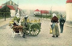 Milchverkäuferinnen auf einer Dorfstraße in Belgien; die Milchkrüge aus Messing stehen auf einer zweirädrigen Holzkarre, die von einem Hund in Zuggeschirr gezogen wird.