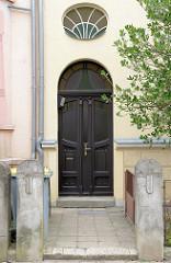 Alte Eingangstür im Stil des Historismus - geschwungene Formgebung des Türblatts, floraler Schnitzerei; Bilder der Architektur in Güstrow.
