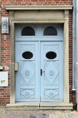 Mit Schnitzwerk verzierte Eingangstür/Doppeltür eines denkmalgeschützten Gebäudes in der historischen Altstadt von Güstrow.