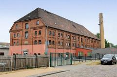 Historische Industriearchitektur, - mehrstöckiges Backsteingebäude Krüppelwalmdach einer Fabrikanlage in der Werkstraße von Güstrow, jetzt Nutzung unter anderem als Bürogebäude / Verwaltungsgebäude.