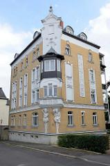 Denkmalgeschütztes Wohnhaus / Eckgebäude in der Straße Am Anger in Altenburg. Eine männliche und weibliche Skulptur - Atlant und Karyatide - stützen einen Erker an der Hausecke.