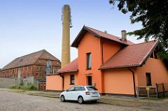 Einzelhaus, Wohngebäude mit knallbunter orangenfarbiger Fassade im Werkweg von Güstrow, dahinter ein Fabrikschornstein und ein mehrstöckiges Backstein-Lagergebäude mit Krüppelweindach.