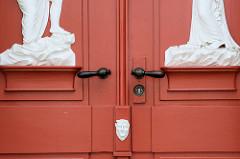 Historische rote Haustür, Doppeltür - klassizistische Schnitzereien und Maskeron unter den Türgriffen - Bilder der restaurierten Altstadt von Güstrow.