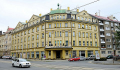 Mehrstöckiges Eckgebäude mit zentralem Eingang, Fassade geschmückt mit figürlichen Reliefs im Stil der Gründerzeit; Architekturbilder aus der Stadt Olmütz / Olomouc.