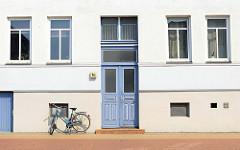 Wohnhaus blau gefasster Eingangstür und schlichter Hausfassade - Architekturbilder aus der Stadt Güstrow.