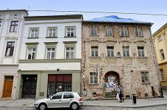 Zwei Wohnhäuser in der Straße 1 Maje von Olmütz / Olomouc; eines ist unbewohnt mit abgebröckeltem Putz und freigelegten Mauersteinen, sowie mit einer Plane abgedeckten Dach. Das andere Gebäude ist renoviert und bewohnt.